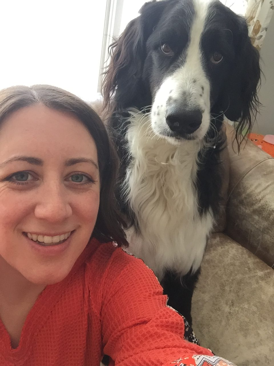 A selfie of a woman in a red orange sweater with a black and white dog