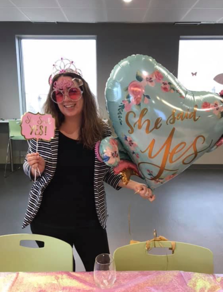 """A woman in black clothes, pink tiara, and pink sunglasses with a floral heart-shaped balloon and a paper sign that says """"she said yes!"""""""