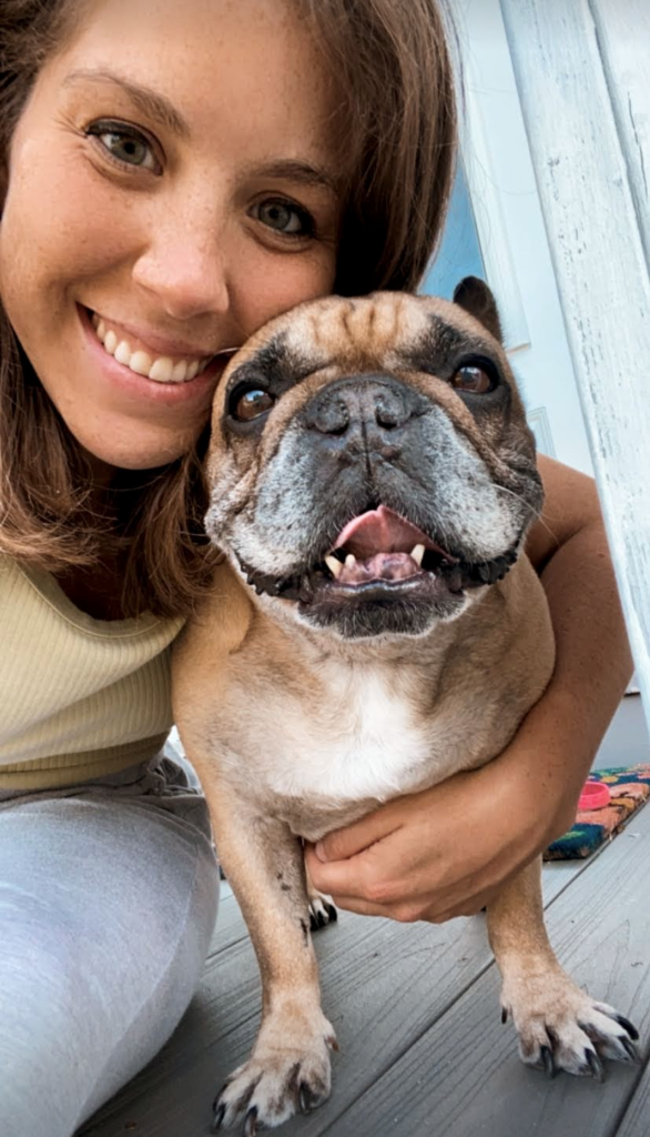 A brunette woman smiling with a French bulldog