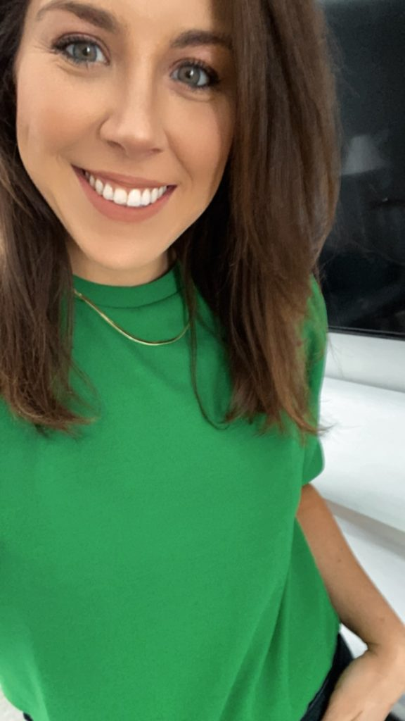 Selfie of smiling brunette woman in green shirt